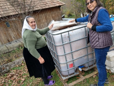 Elena shows Rebecca how the apples are fermented for four months before distilling.