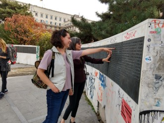Dana shows Rebecca some names on the wall that honors those who died in the 1989 Revolution.