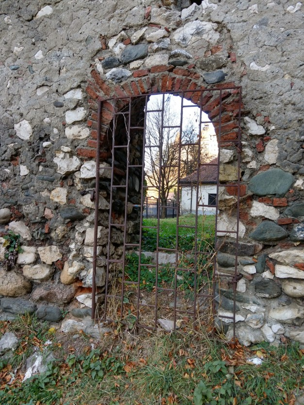 """Off to the side of the road near a turn-out in the road, I found this un-celebrated, locked off gate in the wall that used to keep outsiders out. This, I think, was the actual """"gate"""" in the Carpathian Gate."""
