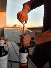 Adi opens wine.