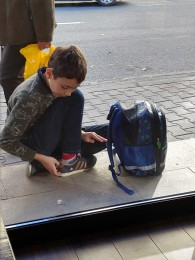 Boy waiting for a ride outside restaurant.